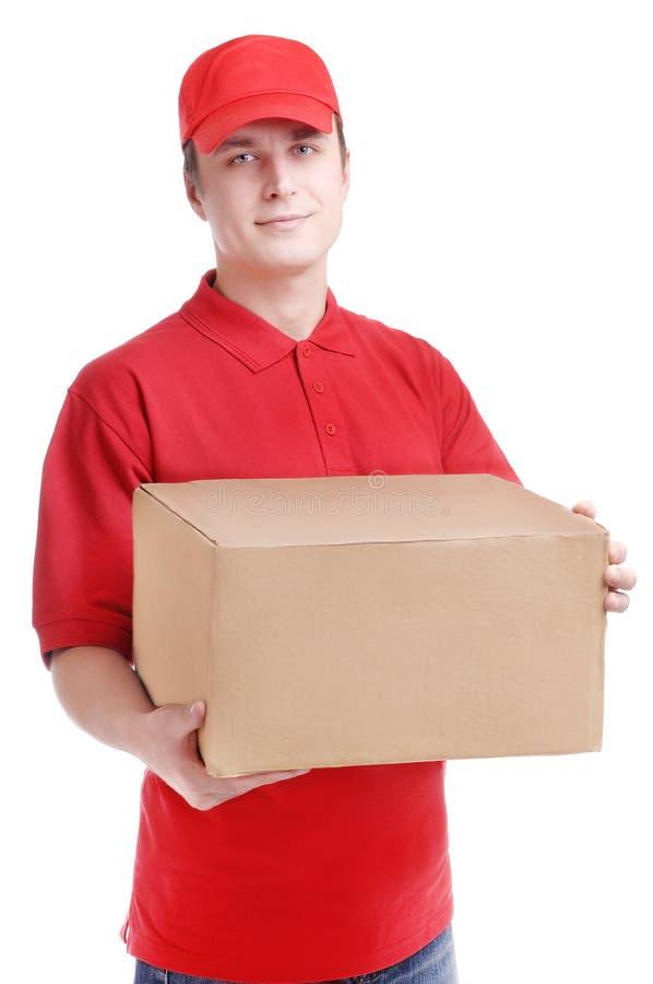 Corriere in uniforme rossa con la casella in mani fotografia stock