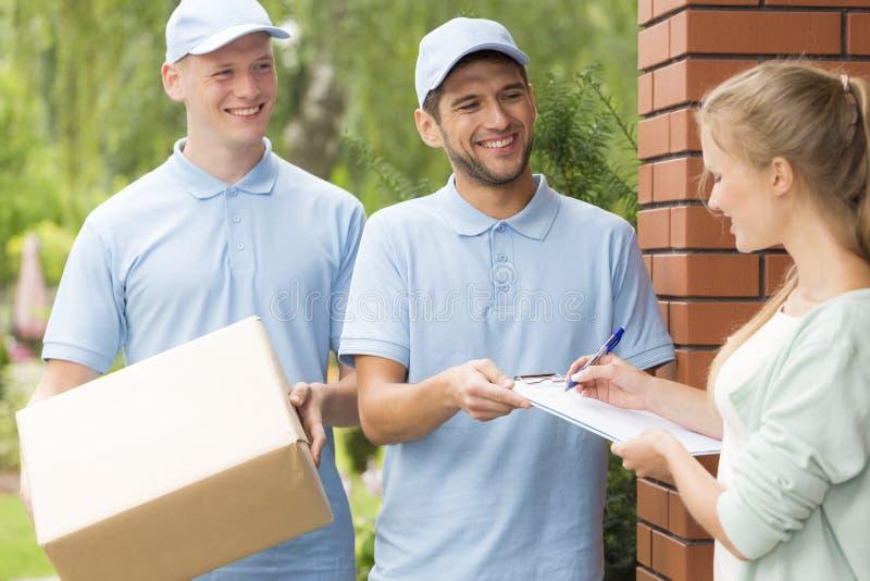 Corrieri bei in uniformi blu che consegnano un pacchetto ad una giovane donna graziosa fotografia stock