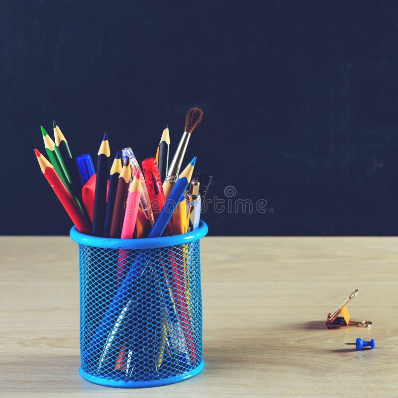 Corrisponda alla penna con le matite e le graffette variopinte sui tum di legno fotografia stock