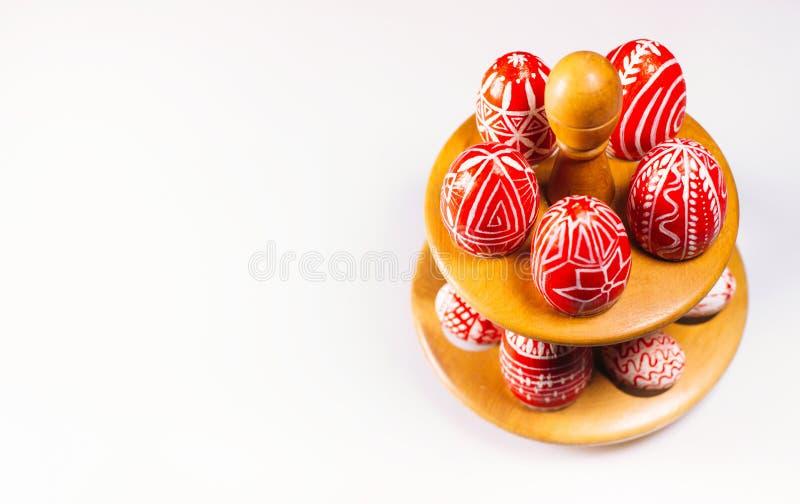 Corrisponda alle uova con le uova rosse di Pasqua con il modello bianco piega e che stanno su fondo bianco Uova tradizionali ucra immagini stock