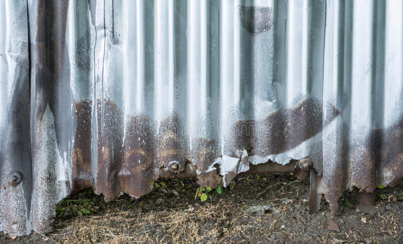 Damaged fence from corrugated iron in city street stock images