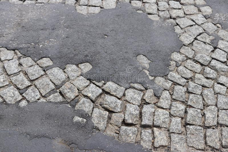 Corrosion of old asphalt laid on a granite pavement in the historic center of the city. Destruction of architectural monuments. Ta. Steless design of the stock photography