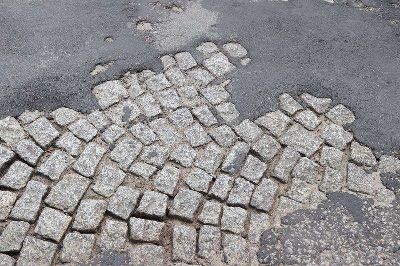 Corrosion of old asphalt laid on a granite pavement in the historic center of the city. Destruction of architectural monuments. Ta. Steless design of the royalty free stock image
