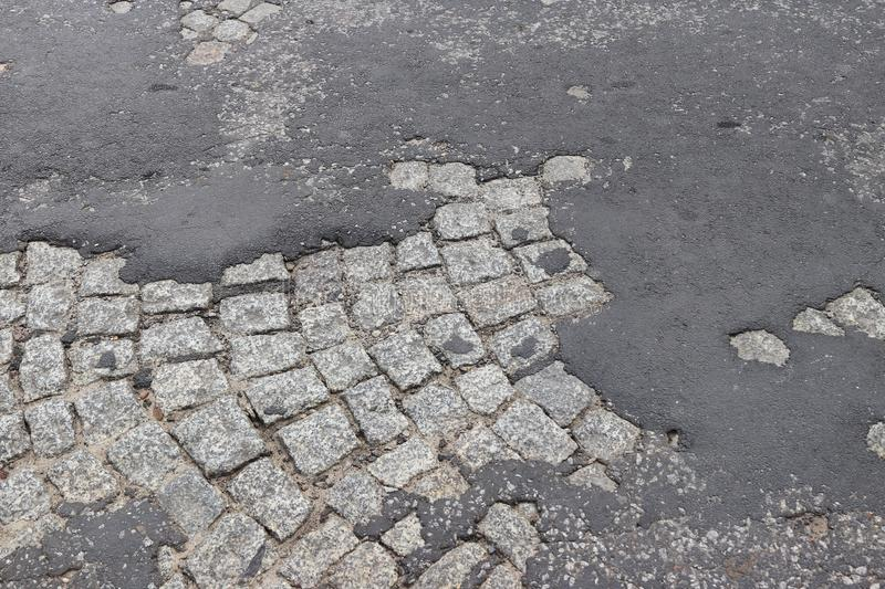 Corrosion of old asphalt laid on a granite pavement in the historic center of the city. Destruction of architectural monuments. Ta. Steless design of the stock images