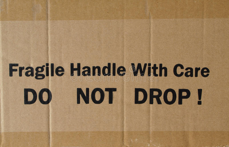 Corrugated cardboard. Fragile Handle with Care Do not drop label on a corrugated cardboard box royalty free stock photo