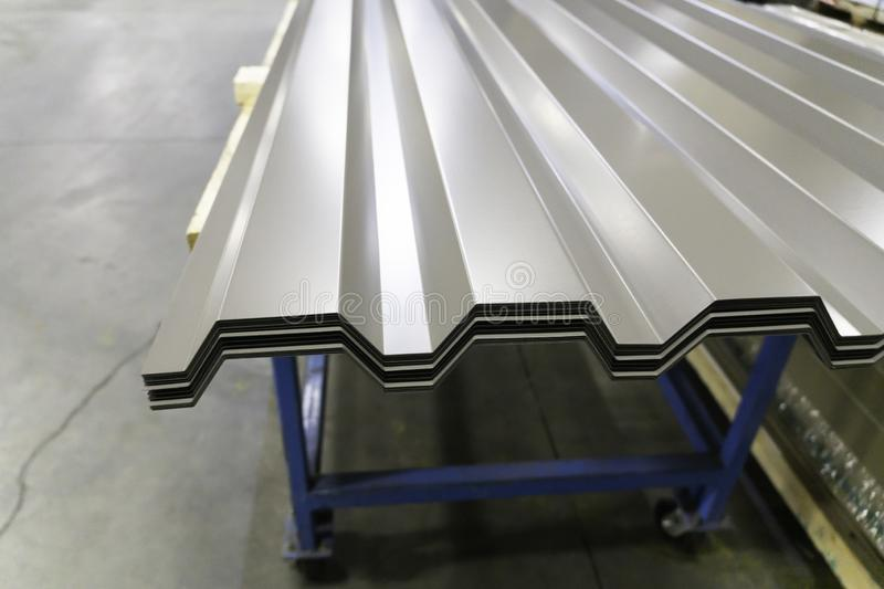 Corrugated galvanised metal roofing sheets on factory workshop. Floor royalty free stock images