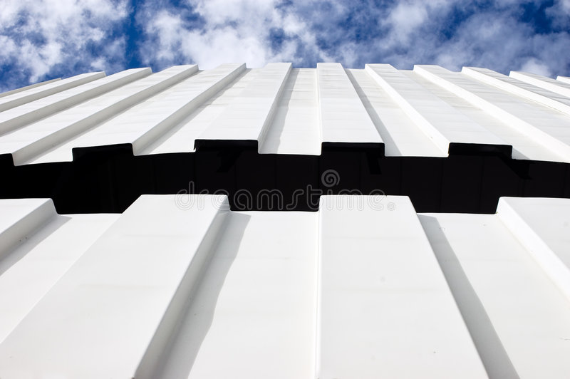 Corrugated iron roof against cloudy sky stock photography