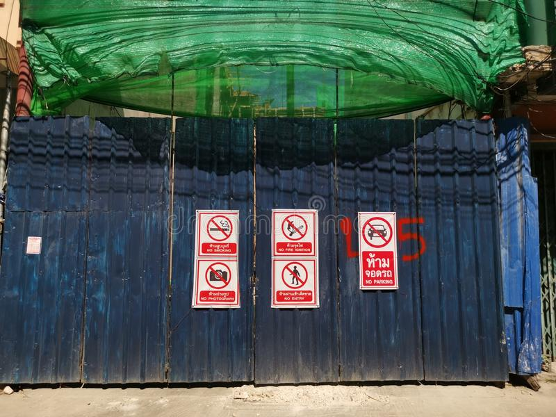 Corrugated metal fence at construction site. Corrugated metal fence covered with prohibition signs at construction site on November 24, 2019 in Thai capital royalty free stock image
