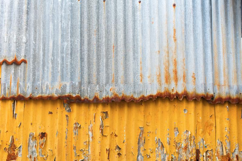 Corrugated rusty colored sheet metal cracked paint stock image
