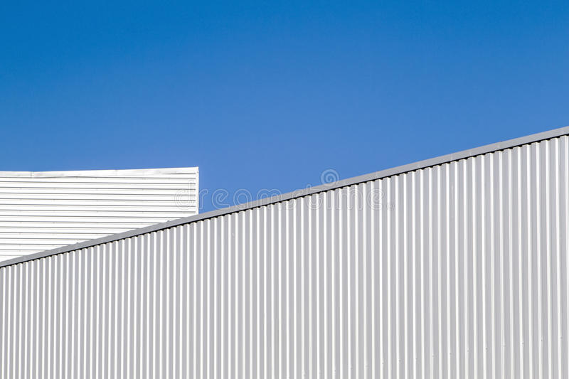 Corrugated sheet metal wall and roof against blue sky. Modern warehouse or storage. Industrial look. Outdoor. Digital royalty free stock photo