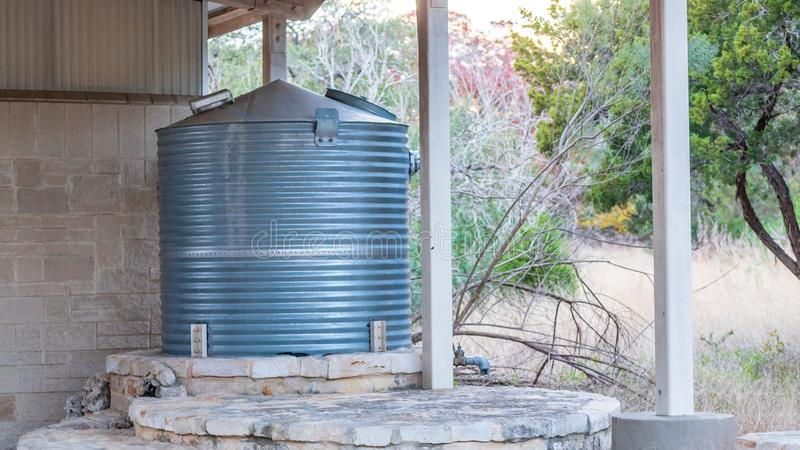 Corrugated steel water storage tank on top of flagstone masonry structure, with small stone fountain in front. Corrugated steel water storage tank on top of a royalty free stock image