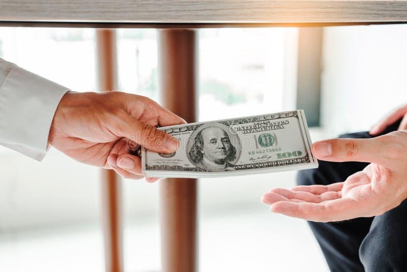 Corrupción y soborno, hombre de negocios que da soborno de la corrupción de los billetes de dólar al director empresarial para tr foto de archivo