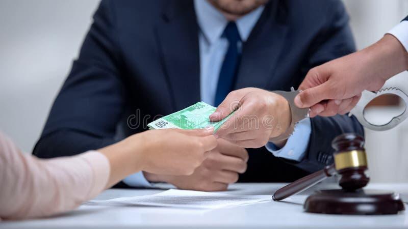 Corrupt attorney handcuffed when taking euro bribe in court, anti-corruption law stock photography