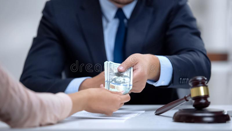 Corrupt lawyer taking dollars bribe from client in court, corruption law royalty free stock photo