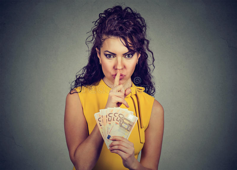 Corrupt, secretive woman with euro money showing shhh sign. On gray background. Bribery concept in politics royalty free stock photo