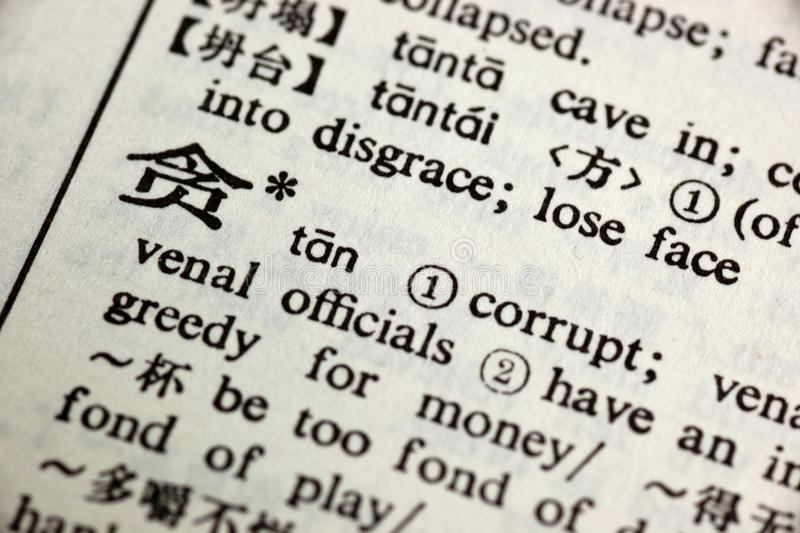 Corrupt written in Chinese. In a Chinese-English translation dictionary stock photos