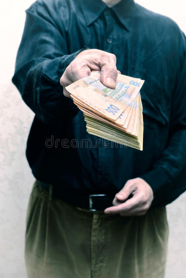 Corrupted businessman, or politician, offering a Hryvnia banknotes bribe. In Ukraine royalty free stock image