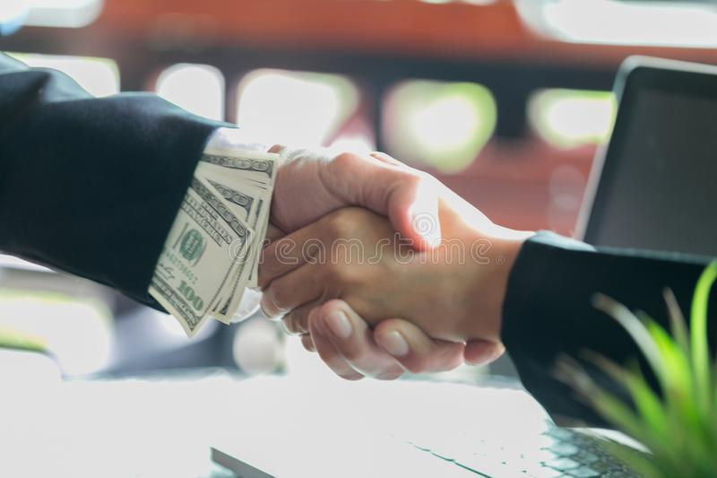 Corrupted businessman sealing the deal with a handshake and receiving a bribe money, anti bribery and corruption concepts.  stock images