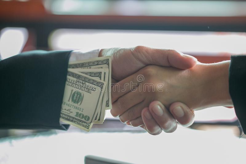 Corrupted businessman sealing the deal with a handshake and receiving a bribe money, anti bribery and corruption concepts.  stock image