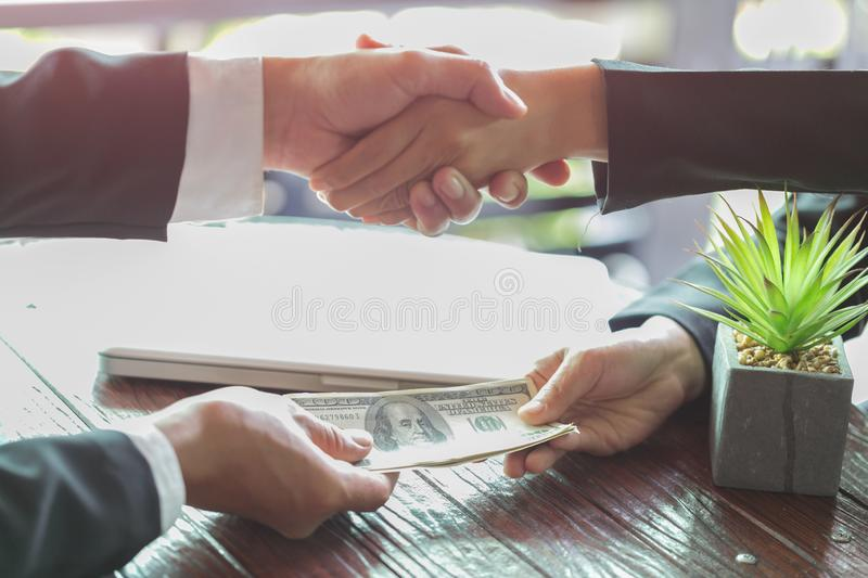 Corrupted businessman sealing the deal with a handshake and receiving a bribe money, anti bribery and corruption concepts.  stock photos