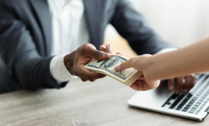 Corrupted businessman sealing deal receiving venality bribe money from partner. Corrupted unrecognizable black businessman sealing the deal receiving venality royalty free stock photos