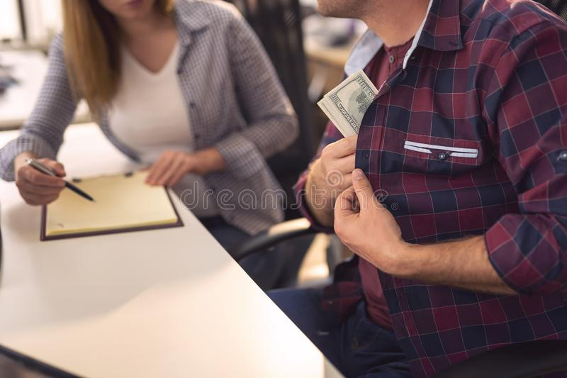 Corrupted businessman taking money. Detail of corrupted businessman taking bribe money in order to sign a contract. Selective focus stock image