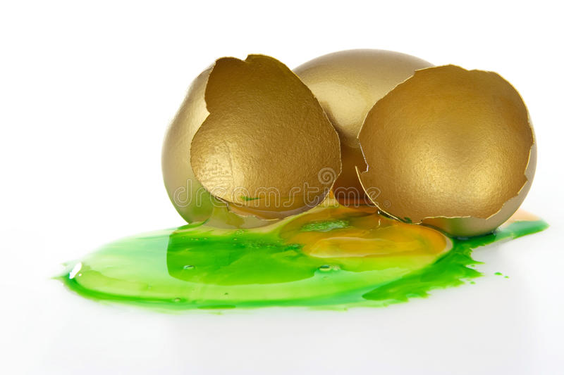 Corrupted gold egg. Corrupted broken gold egg on white background royalty free stock photography