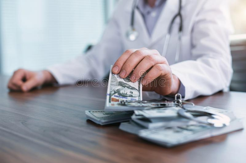Famous doctor taking bribes in his office stock photo