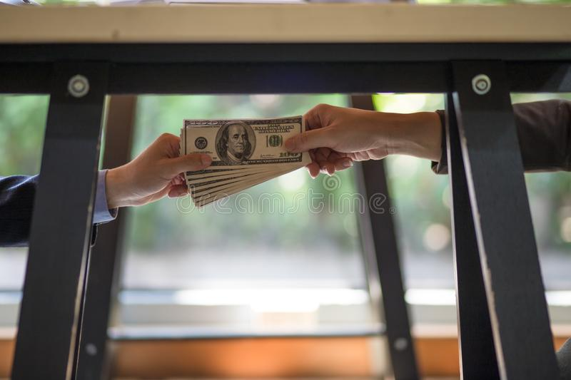 Corrupted two businessman sealing the deal with a handshake and receiving a bribe money. Hands passing money under table corruption bribery stock photos