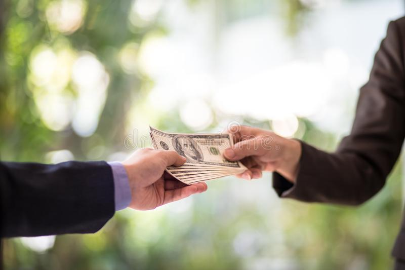 Corrupted two businessman sealing the deal with a handshake and receiving a bribe money. Hands passing money corruption bribery. Corrupted two businessman stock photography