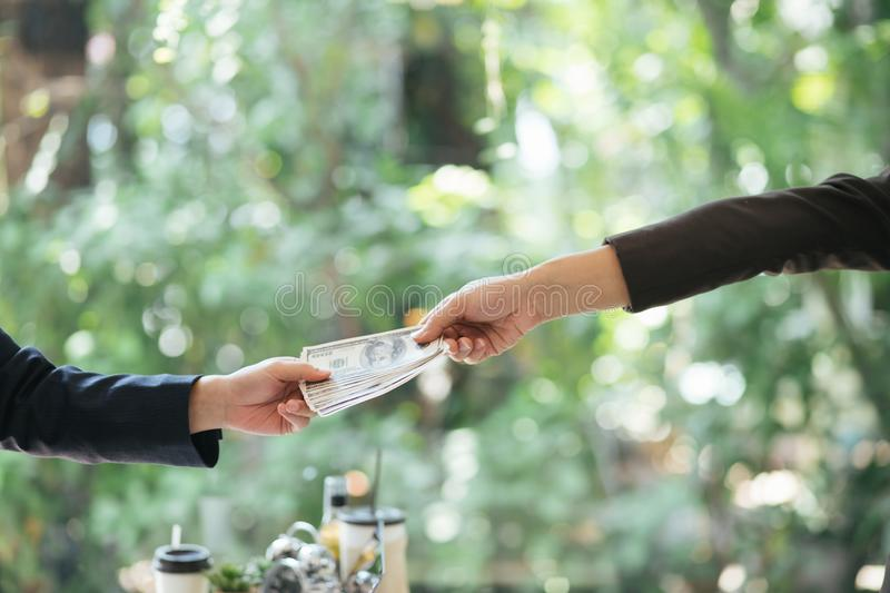 Corrupted two businessman sealing the deal with a handshake and receiving a bribe money. Hands passing money corruption bribery.  royalty free stock images