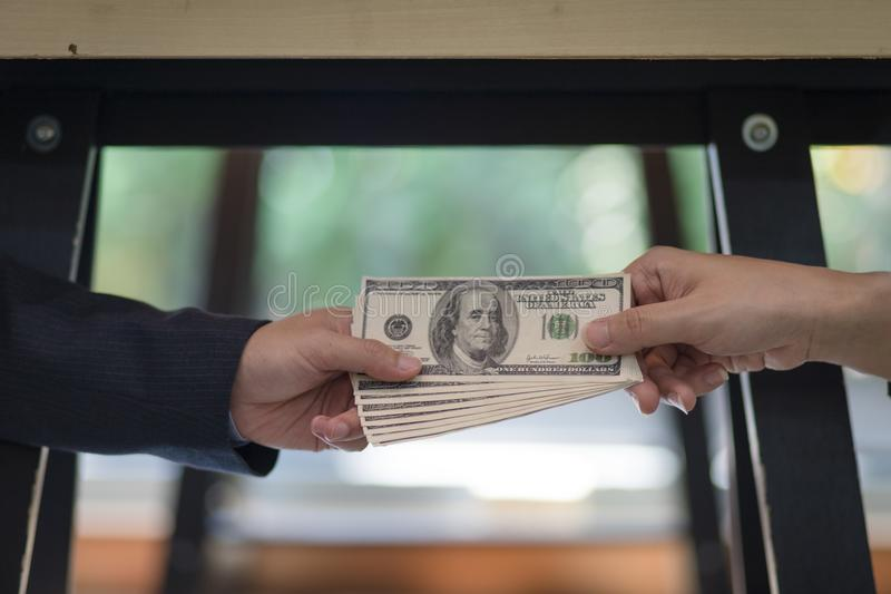 Corrupted two businessman sealing the deal with a handshake and receiving a bribe money. Hands passing money under table corruption bribery royalty free stock image