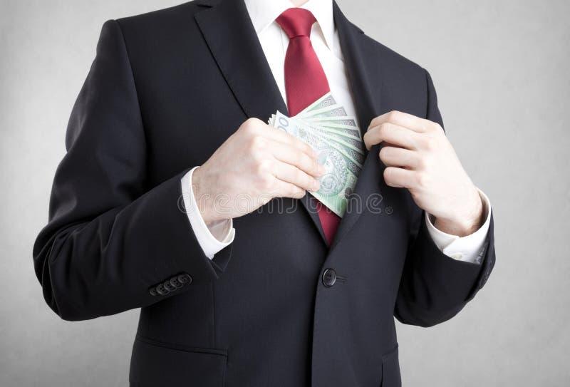 corruptie Mens die poetsmiddelgeld in de zak van het kostuumjasje zetten stock fotografie