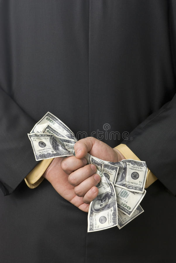 Corruption. Dirty money grasped by a business man behind his back royalty free stock image
