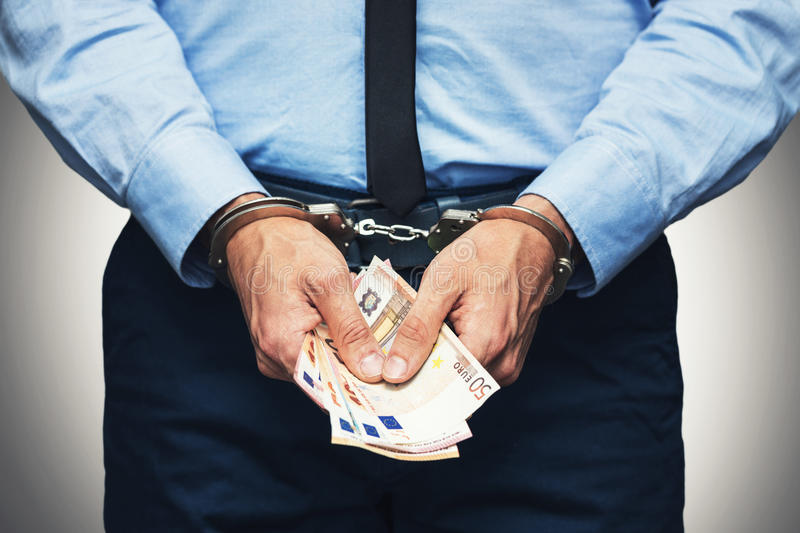 Corruption and bribery concept - arrested official with money. In hands stock photo
