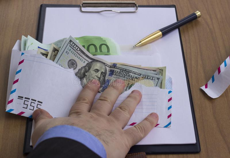 Corruption and bribery. Money in an envelope for signing the document stock photo