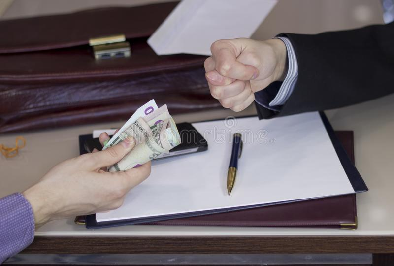 Corruption and bribery. Money in an envelope for signing the document. The person shows Fig stock image