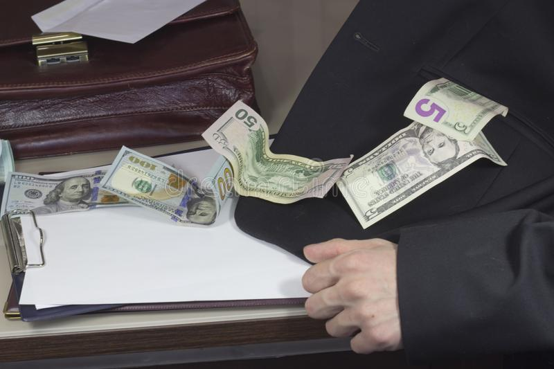 Corruption and bribery. Money flows into the jacket pocket royalty free stock photography