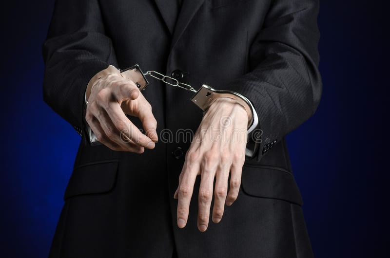Corruption and bribery theme: businessman in a black suit with handcuffs on his hands on a dark blue background in studio isolated. Corruption and bribery theme royalty free stock photography
