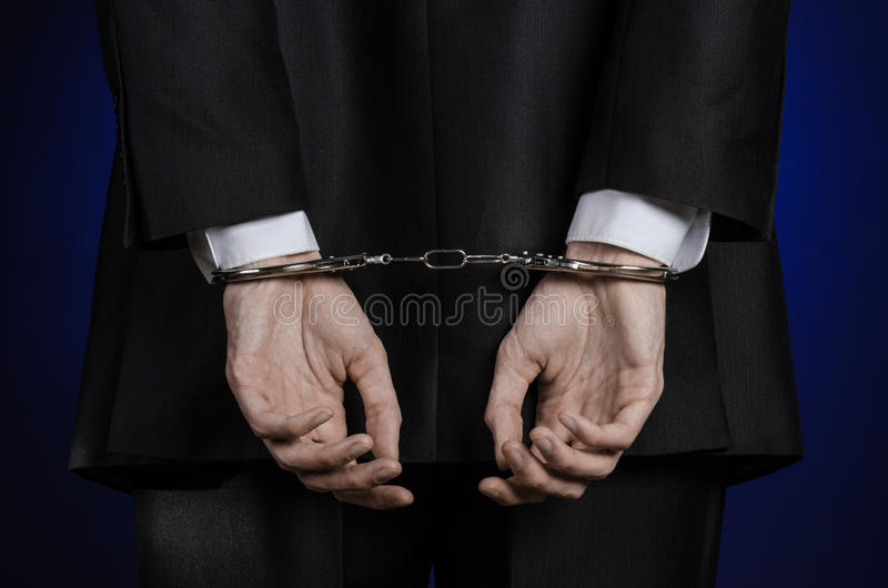 Corruption and bribery theme: businessman in a black suit with handcuffs on his hands on a dark blue background in studio isolated. Corruption and bribery theme stock photography