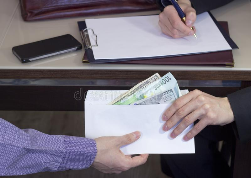 Corruption and bribery. The transfer of a bribe in the envelope royalty free stock image