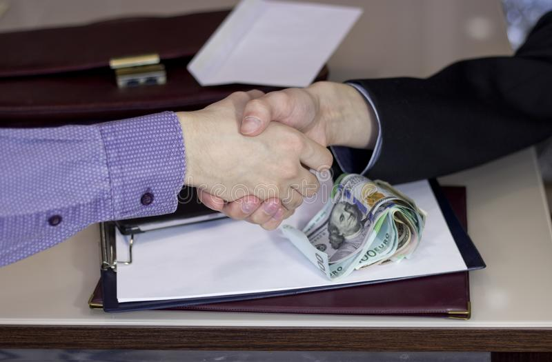 Corruption and bribery. The transfer of a bribe in the handshake stock photo