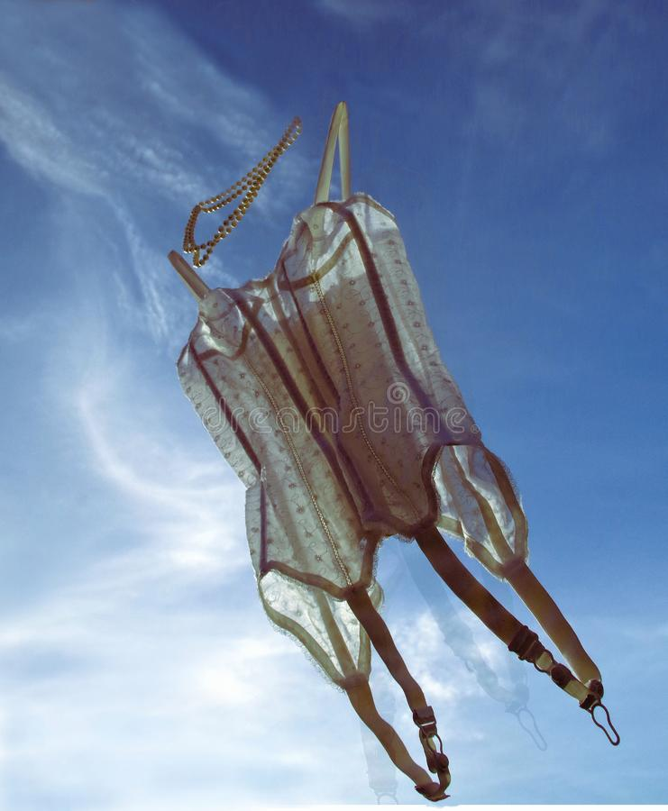 Corsé blanco con el vuelo de los cordones en el cielo fotos de archivo