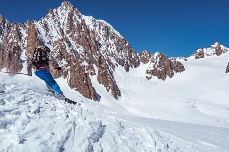 Corsa con gli sci dell'uomo dello sciatore sul ghiacciaio o pendio nevoso con polvere fresca Supporto del massiccio di Mont Blanc fotografia stock libera da diritti