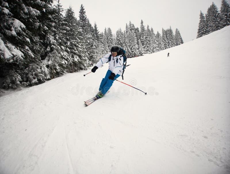 Corsa con gli sci dell'uomo sul pendio fotografia stock