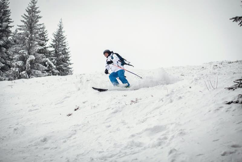 Corsa con gli sci dell'uomo sul pendio fotografie stock