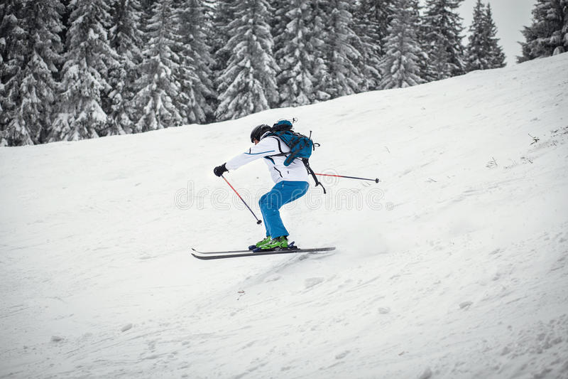 Corsa con gli sci dell'uomo sul pendio immagini stock