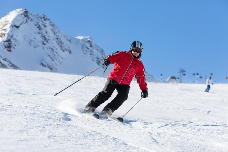 Corsa con gli sci dello sciatore sul pendio dello sci immagini stock libere da diritti