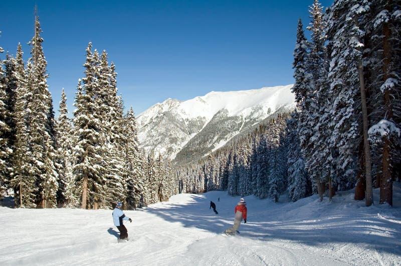 Corsa con gli sci e snowboard sui pendii di montagna immagini stock