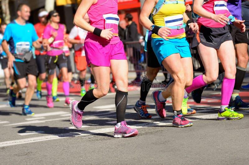 Corsa corrente maratona, piedi dei corridori delle donne sulla strada fotografie stock libere da diritti